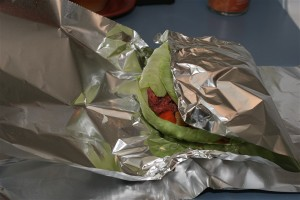 Start wrapping up your meal by folding one end of the top layer of foil over the meal.